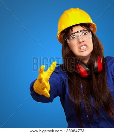 Portrait Of A Frustrated Female Worker On Blue Background