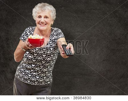 portrait of happy senior woman looking the tv against a grunge wall