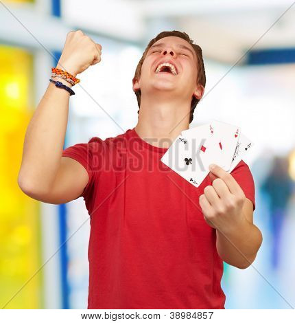 portrait of young man doing a winner gesture playing poker indoor