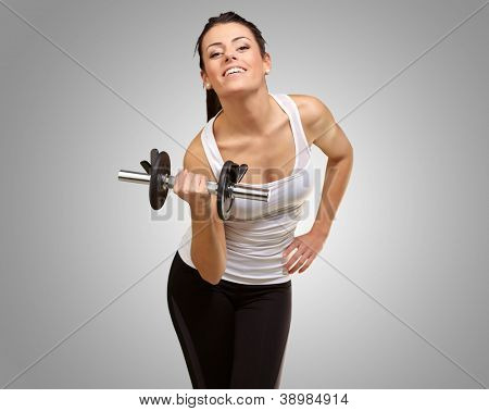 Young woman holding dumbbells isolated on gray background