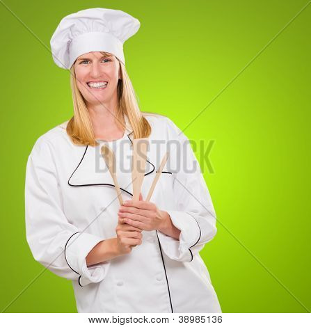 Female Chef Holding Wooden Spoon against a green background
