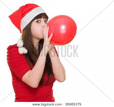woman wearing a christmas hat and blowing a balloon against a white background