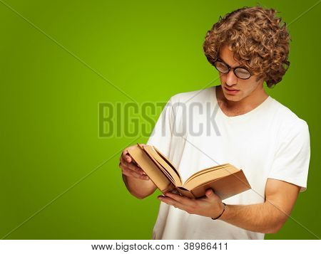 Portrait Of A Man Reading A Book Isolated On Green Background