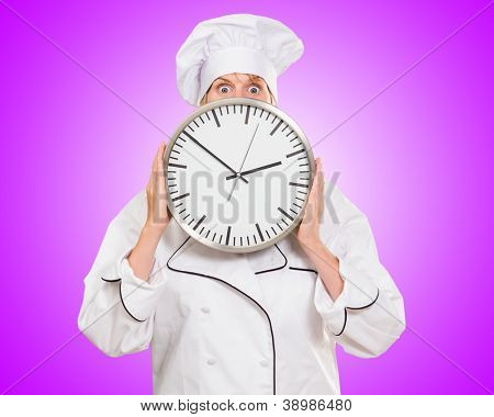 worried chef hiding behind a clock against a pink background