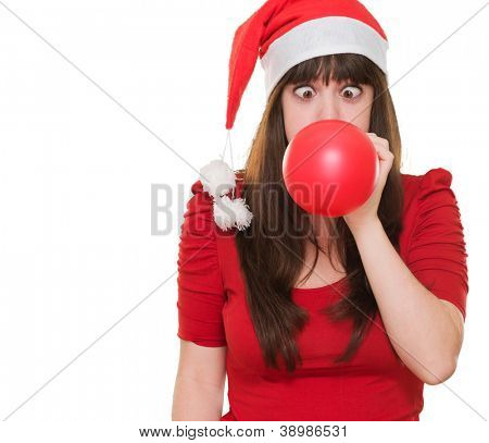 christmas woman blowing a balloon with her eyes crossed against a white background