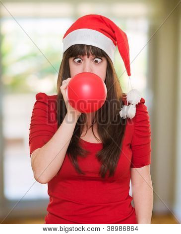 christmas woman blowing a balloon with her eyes crossed, indoor
