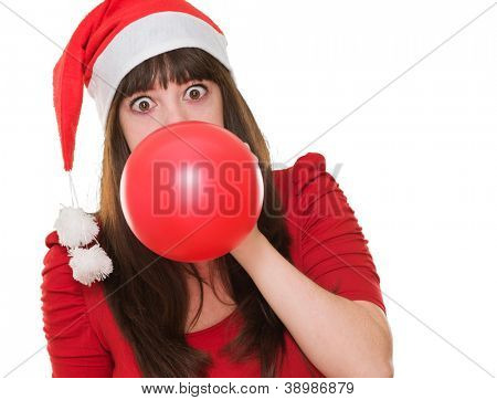 woman blowing balloon and wearing a christmas hat against a white background