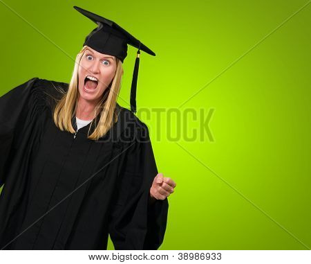 Portrait of an angry graduate against a green background