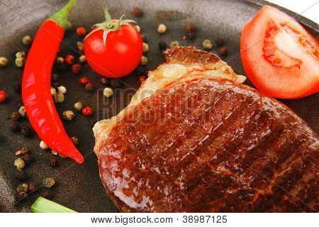 meat savory : platter of grilled beefsteak served with hot cayenne peppers red tomato green chives on metal pan isolated over white background