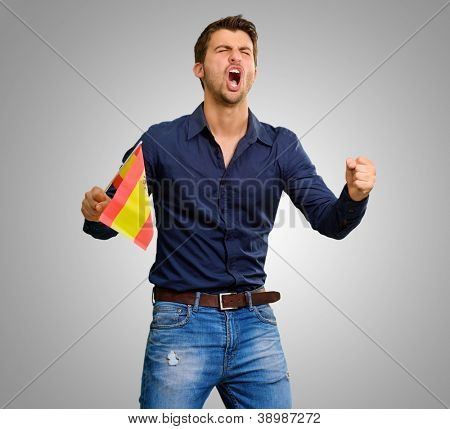 Man cheering and holding flag on grey background