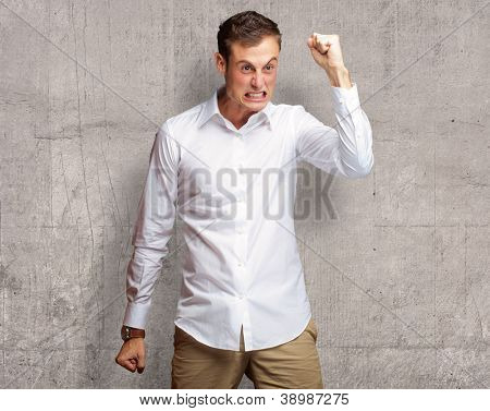 Portrait Of Angry Young Man Clenching His Fist, Indoor