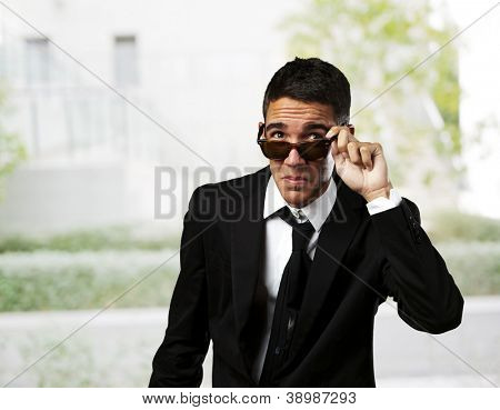 portrait of business man taking off the sunglasses against a park
