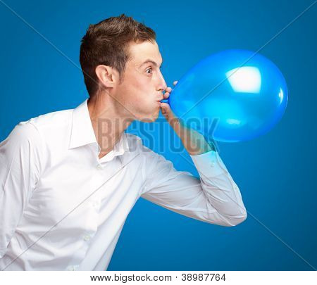 Portrait Of Young Man Blowing A Balloon Isolated On Blue Background