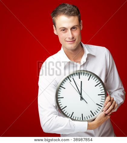 Happy Man Holding Clock In His Hand On Red Background