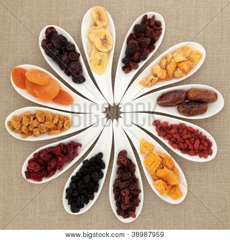 Large dried fruit selection in white porcelain dishes over beige linen background.