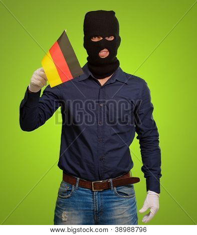 Man wearing robber mask and holding flag on green background