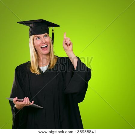 Graduate Woman Holding Digital Tablet against a green background