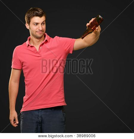 Portrait Of Young Man Holding Empty Bottle On Black Background
