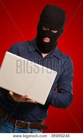 jovem ladrão macho segurando laptop isolado em fundo vermelho