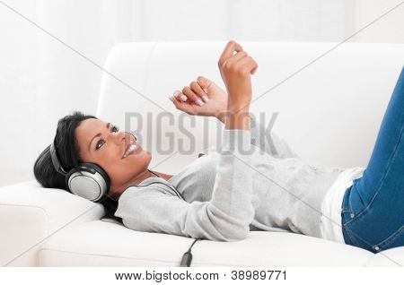 Young beautiful woman listening music while relaxing on sofa at home