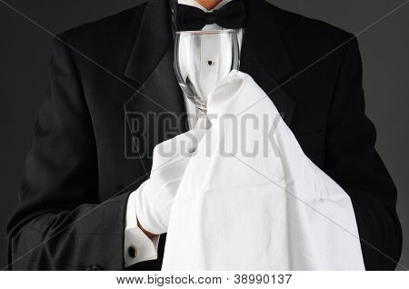 Closeup of a waiter wearing a tuxedo polishing a wine glass. Horizontal format on a light to dark gray background. Man is unrecognizable.