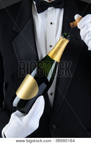 Closeup of a Sommelier uncorking a champagne bottle. Man is unrecognizable wearing a tuxedo and white gloves. Vertical Format.