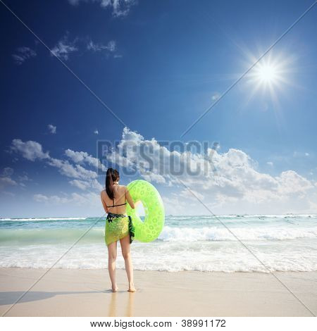 Young woman standing on sand with lifebelt