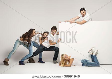 Jóvenes empujando tablero blanco