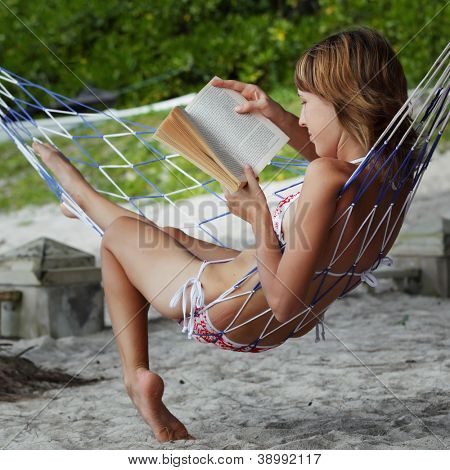 Close up portrait of a young woman reading a book lying in a hammock on tropical resort