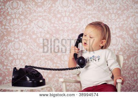 kleines Baby mit alten Jahrgang Telefon vor retro Hintergrund