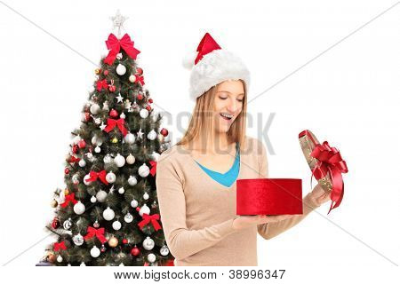 Excited female with christmas hat opening a gift and decorated christmas tree in the background