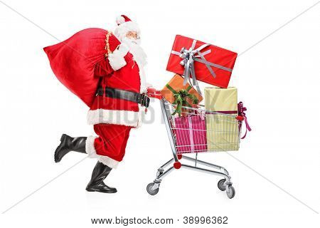 Santa Claus carrying a bag and pushing a shopping cart full of gifts isolated on white background