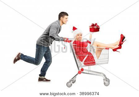 Happy guy pushing a female wearing christmas costume in a shopping cart isolated on white background