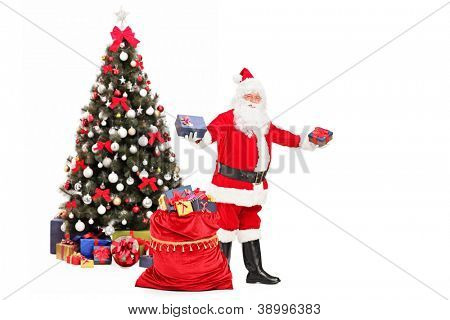 Santa Claus giving gifts from a bag full of presents and decorated christmas tree in the background