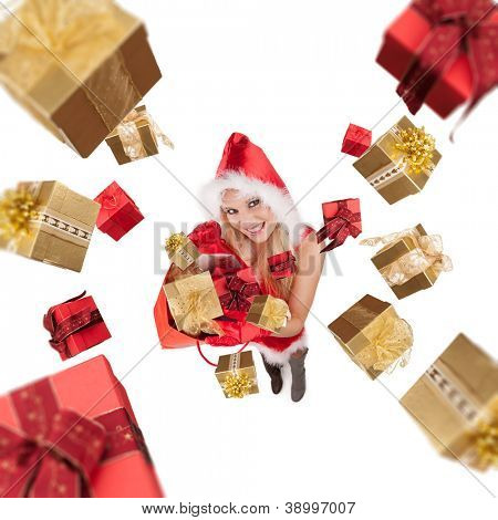 Attractive young blond woman in santa costume throwing christmas gifts. Studio shot, isolated on white background. Upper gifts are blurred to create motion effect