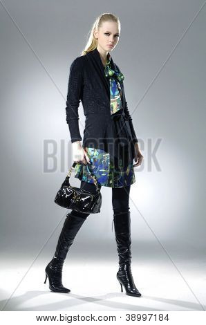 fashion model holding handbag posing walking in studio