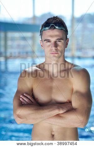 Glücklich muskulös Schwimmer trägt Brille und Cap mit Swimming Pool und darstellen-Gesundheit und Fit-Konzept