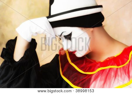 Unhappy pierrot clown leaning on her white glove hand