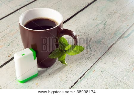 Little white box of tablets as sweetener for a mug of coffee