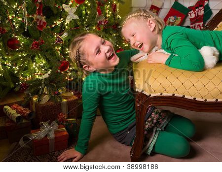 Laughing little sisters near their christmas tree and presents
