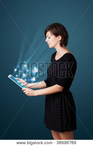 Young business woman looking at modern tablet with abstract lights and social icons