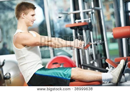 fitness man doing back muscles exercises with training weight machine station in gym
