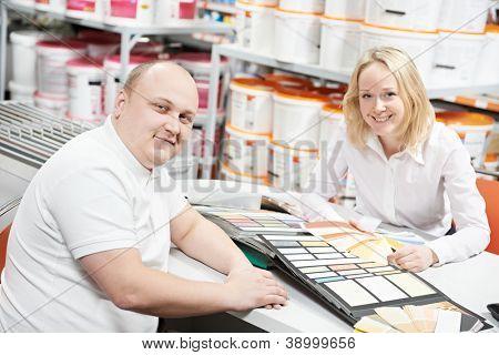 Ayuda asistente vendedor para elegir la pintura color y demostrando que empareja las muestras al comprador en hardware s