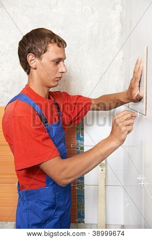 tiler fixing wall tile at home repair renovation work with spacer