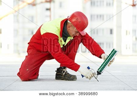 builder filling joint of concrete board with industrial polyurethane sealing foam in protective workwear at construction area