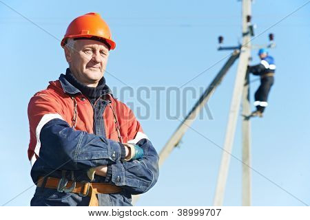 Portrait of electrician lineman repairman worker on electric post power pole line work