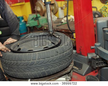 Professional auto mechanic changing a tire in auto repair shop