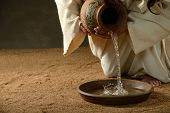 image of priest  - Jesus pouring water from a jug  - JPG
