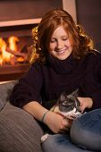 image of fondling  - Happy teenage girl sitting at fireplace at home fondling cat smiling - JPG