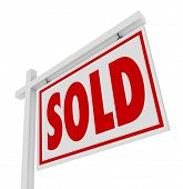 A white real estate for sale sign with the word Sold representing a successfully closed home, house